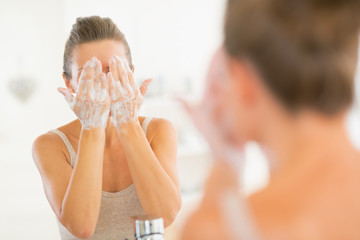 Young woman washing face in bathroom