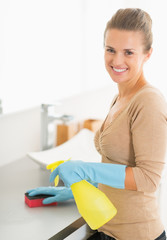 Portrait of smiling housewife cleaning desk in bathroom