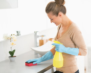 Housewife cleaning desk in bathroom
