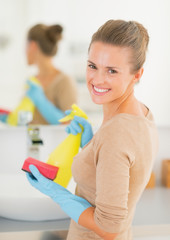 Smiling housewife with spray bottle and sponge in bathroom