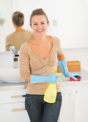 Portrait of happy housewife with spray bottle and sponge in bath