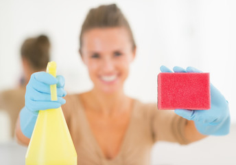 Closeup on happy young housewife showing spray bottle and sponge