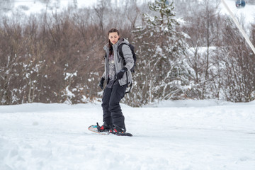 An engrossed female snowboarder is skiing with her snowboard