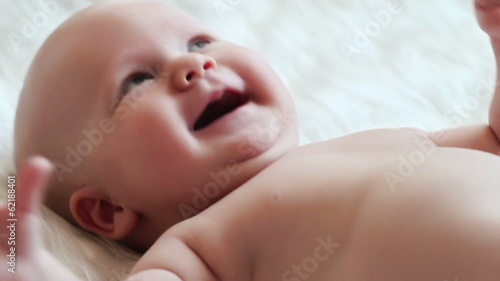 Happy newborn baby smiling close-up in white bed