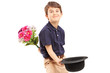 Smiling kid holding bunch of flowers and hat