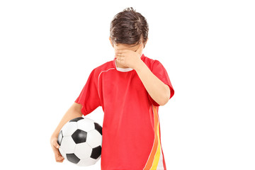 Sad boy with soccer ball