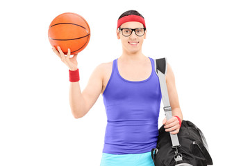Young male athlete with sports bag holding a basketball