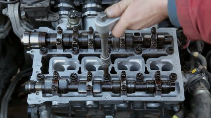 Mechanic fixing camshaft of car engine with socket wrench