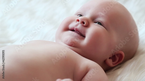 Happy newborn baby smiling closeup
