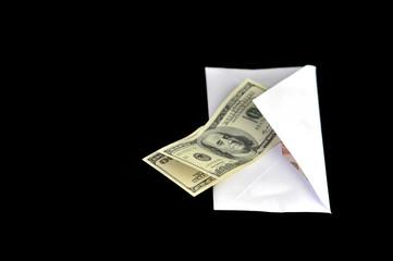 Dollar bills in white envelope isolated on black background