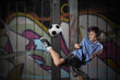 A young boy plays street soccer against a graffiti covered wall