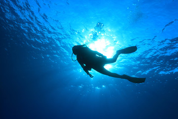 Silhouette of scuba diver in the ocean