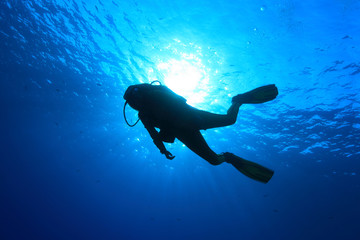 Scuba diver and sunlight in the blue water