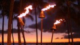 Tiki fire torch sunset evening Hawaii beach Waikiki