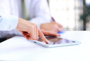 Close-up of a modern business team using tablet