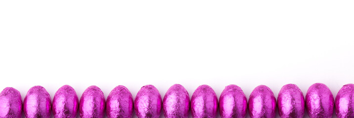 Row of mini chocolate eggs wrapped in pink foil