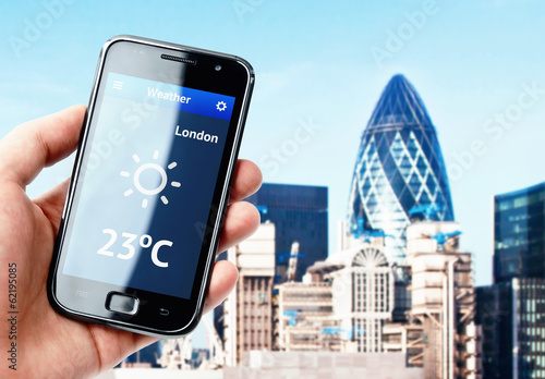 Hand holding smartphone with weather in London