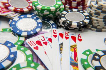 Royal flush poker hand with poker chips stack