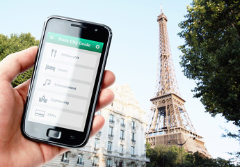 Hand holding smartphone with city guide in Paris