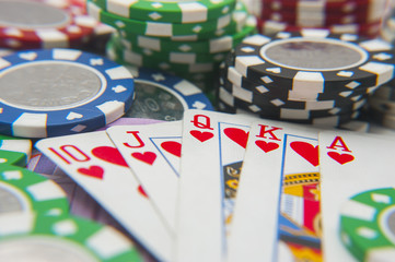Royal flush poker hand with poker chips stack