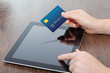 female hands holding credit card and a computer on the table in