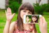 female hand holding a phone with video call of little girl on th