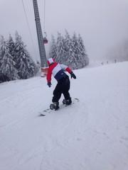 snowboarder beim fahren auf der piste