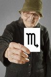 Elderly woman holding card with printed horoscope Scorpio sign.
