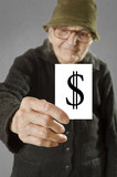 Elderly woman holding card with printed dollar mark.