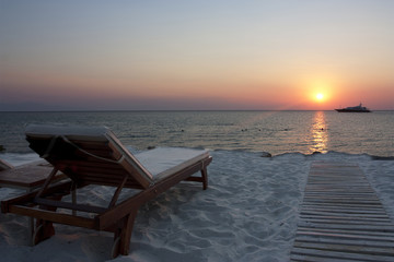 empty sun lounger at sunset on beach with boat