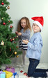 Kids decorating Christmas tree with baubles in room