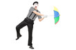 Mime artist holding an umbrella simulating being blown by wind