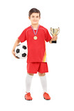Junior football player holding a golden cup