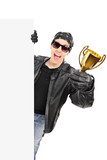 Male biker standing behind blank panel and holding a trophy