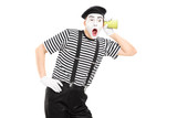 Male mime artist listening through wall with a cup
