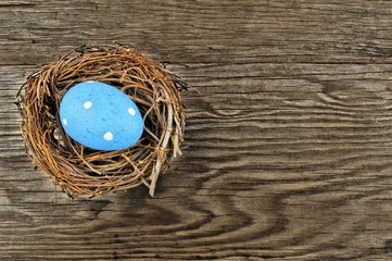 Single blue Easter egg in nest over a wooden background