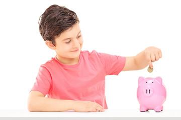 Boy putting money into a piggybank