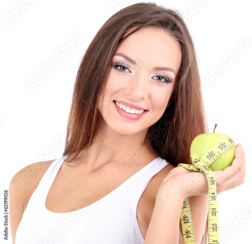 Beautiful young woman with green apple and measuring tape