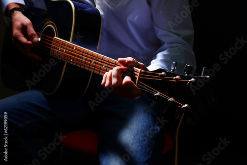 Young musician playing acoustic guitar, close up,