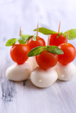 Tasty mozzarella cheese with basil and tomatoes, on wooden