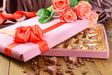 Delicious chocolates in box with flowers