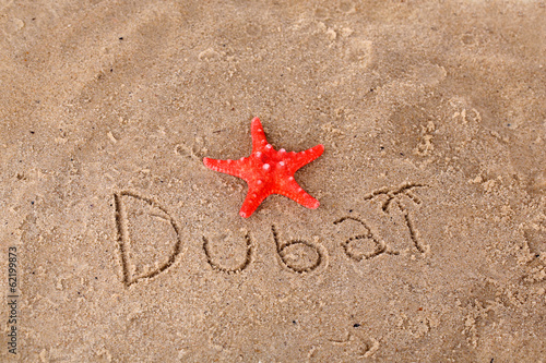 Inscription Dubai in wet sand close-up background