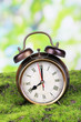 Retro alarm clock on grass on natural background