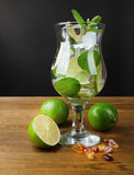 Ingredients for lemonade in glass, on grey background