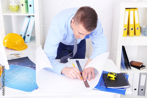 Confident young architect working at office