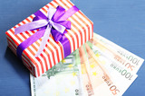Gift box with money  on color wooden background