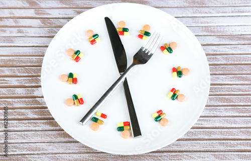 Medication schedule and meals. Conceptual photo. On wooden