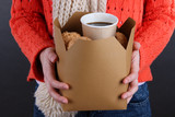 Woman holds box with coffee and cookies on black background