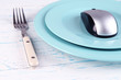 Computer mouse on plate with fork on wooden background