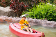 Happy boy paddling kayak on the river and enjoying a lovely summ